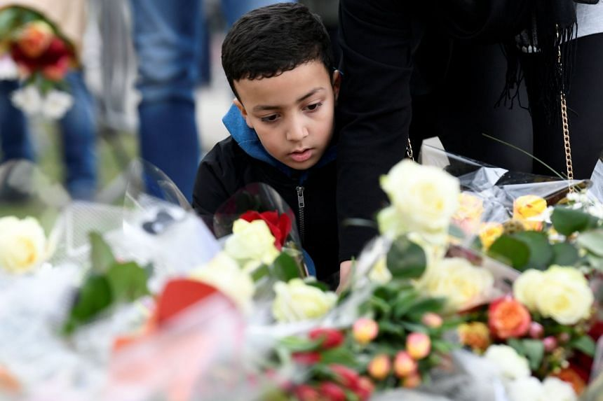 A child places flowers at a makeshift memorial at the site of a tram shooting in Utrecht.