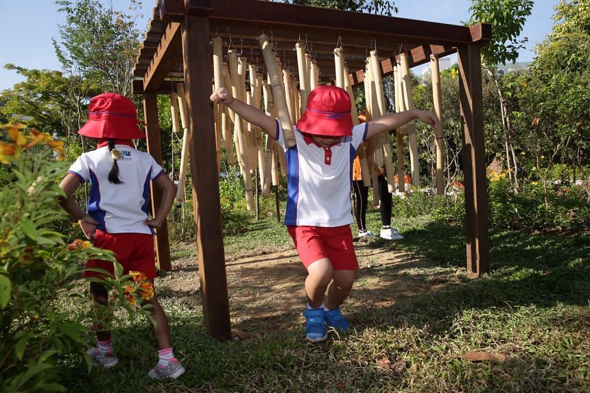 A preschool pupil making music by running through hanging bamboo poles in the new Nature Playgarden at HortPark on March 19, 2019.