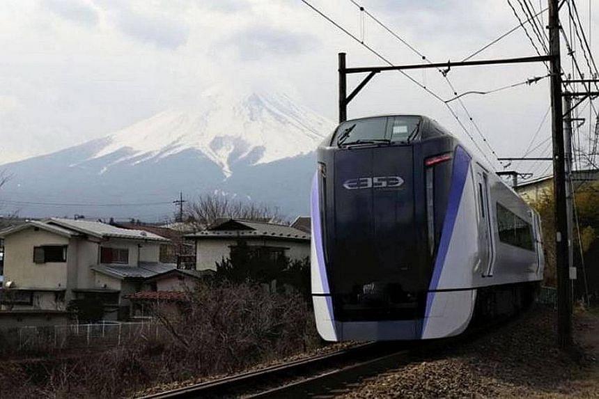 The Fuji Kaiyu limited express train in Fujiyoshida, Yamanashi prefecture, with the Unesco World Heritage site Mount Fuji in the background.