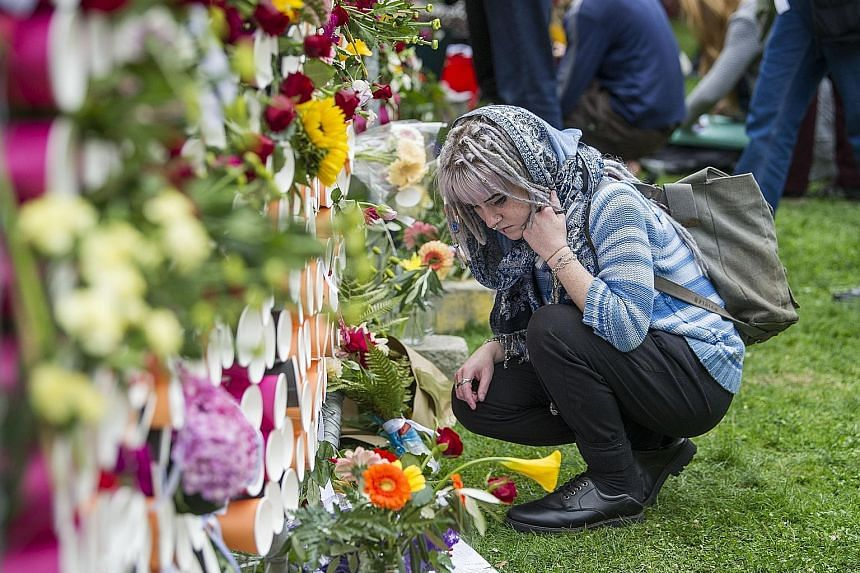 A student at a makeshift memorial at Christchurch's University of Canterbury yesterday, following a vigil to commemorate the victims of last Friday's mass shooting.