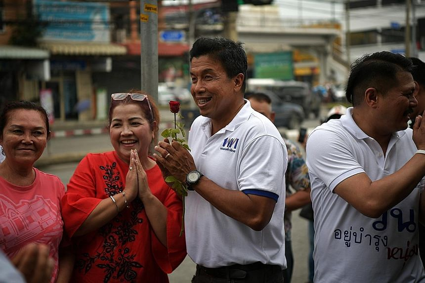Dr Chadchart Sittipunt (centre), one of three Pheu Thai candidates for prime minister, campaigning last Saturday with fellow party member Wan Yubamrung, who is contesting in the Bang Bon district of Bangkok.