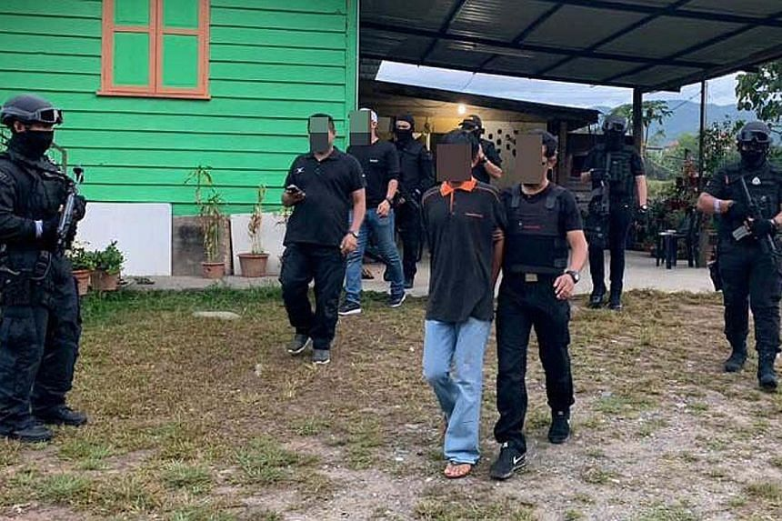 Malaysian security officers taking away a suspected militant in Semporna, Sabah, during the latest anti-terror raids.