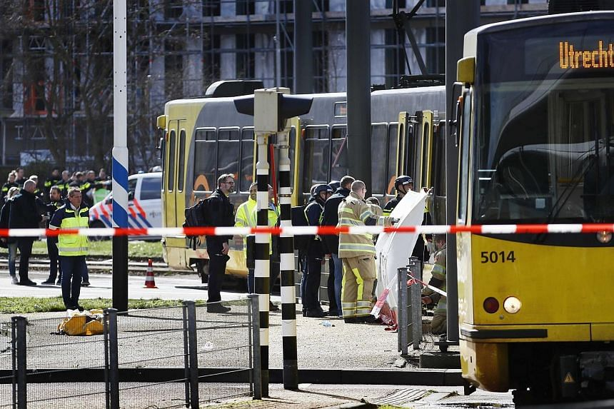 Emergency workers responding to a shooting on a tram in the Dutch city of Utrecht yesterday. The police are hunting for a 37-year-old man born in Turkey in connection with the incident, which has been described as a possible terror attack.