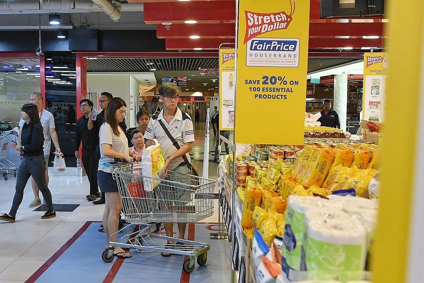 Shoppers at the FairPrice Xtra outlet in Kallang Wave Mall yesterday. The 100 house brand products whose prices have been frozen include rice, cooking oil, poultry, toiletries and household cleaning items.