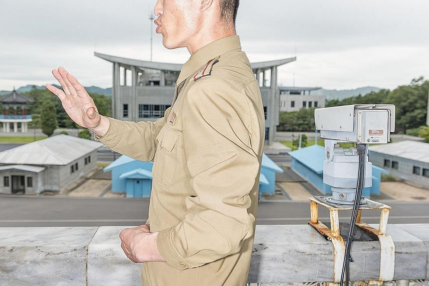 A man having a go at a shooting game at Rungna Dolphinarium in North Korea, where families gathered to celebrate National Liberation Day on Aug 15. Above: Lunchtime on a boat on Taedong River, with the state TV channel broadcasting images of artiller