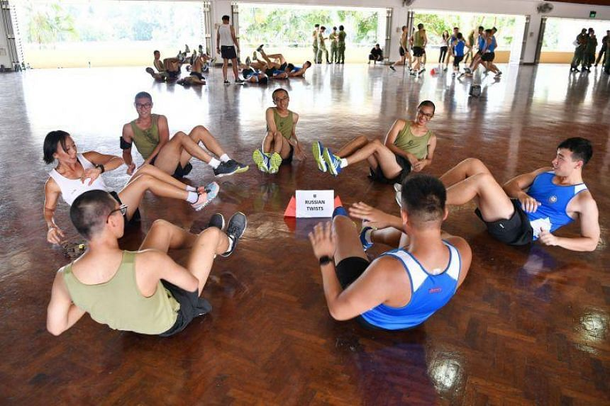 """Recruits exercising at School Five of the Basic Military Training Centre yesterday. """"The mission and purpose of School Five is to transform recruits into confident, competent and committed soldiers,"""" said its commanding officer, LTC Sim Kian Hwa."""