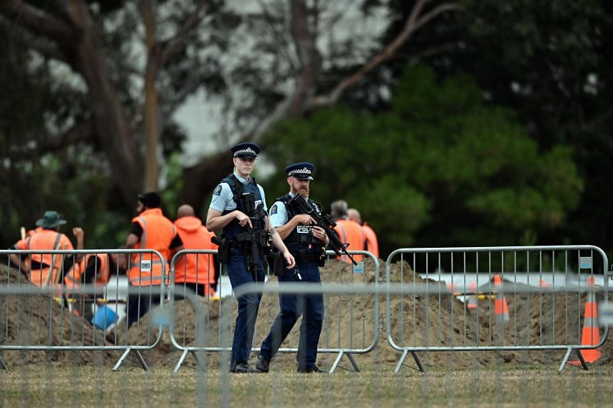 Police patrol a cemetery as workers prepare grave sites for the victims of the Christchurch attacks, early on March 19, 2019.
