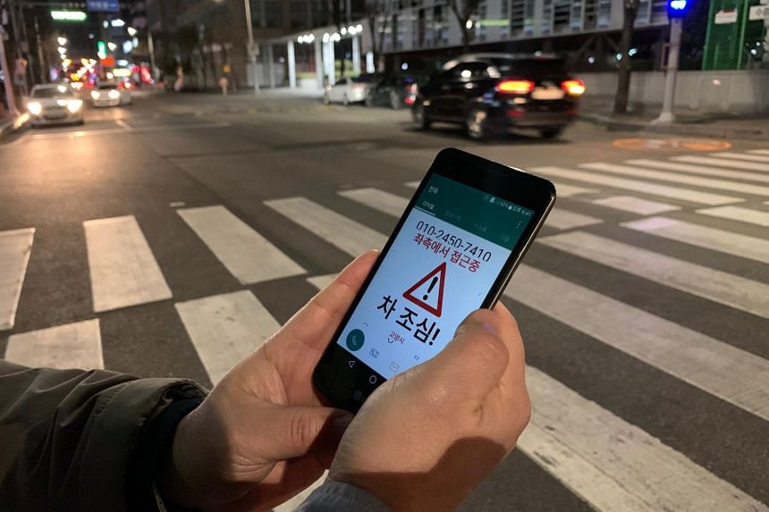 Kim Jong-hoon, a senior researcher, demonstrates an application that gives alerts to users distracted by using smart phones while crossing the road.