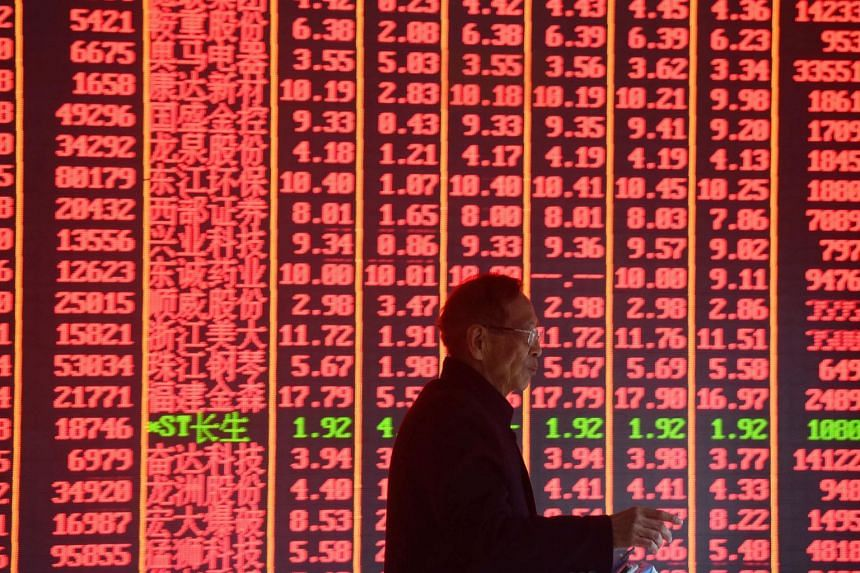 A man in front of an electronic board showing stock information at a brokerage house in Hangzhou, Zhejiang province, China, on Feb 11, 2019.