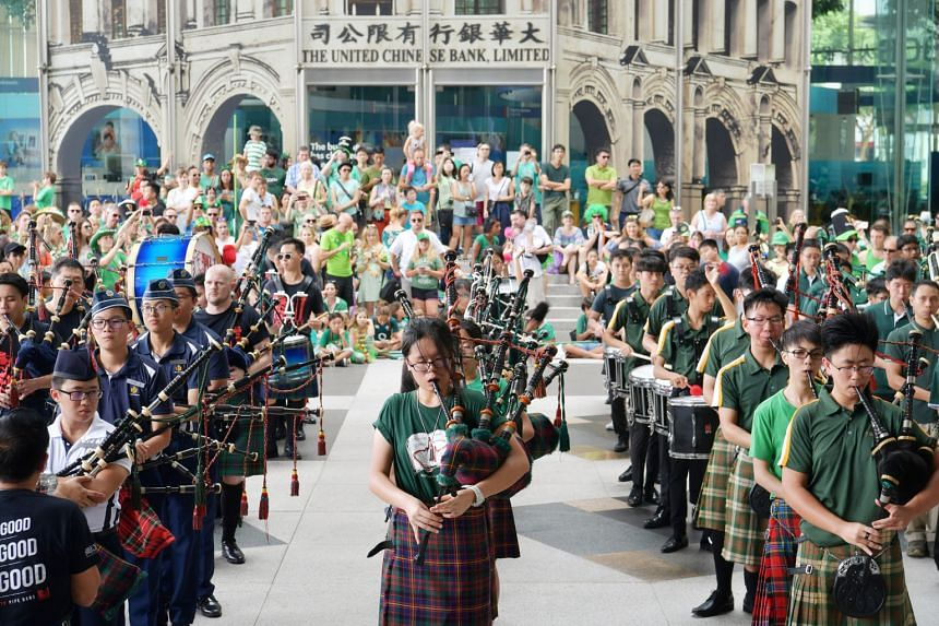 Members of pipe organ bands from several schools in Singapore, including St Joseph's Institution and Raffles Girls' School, performing at the St Patrick's Day parade at UOB Plaza in Raffles Place. About 400 people from the Irish community in Singapor