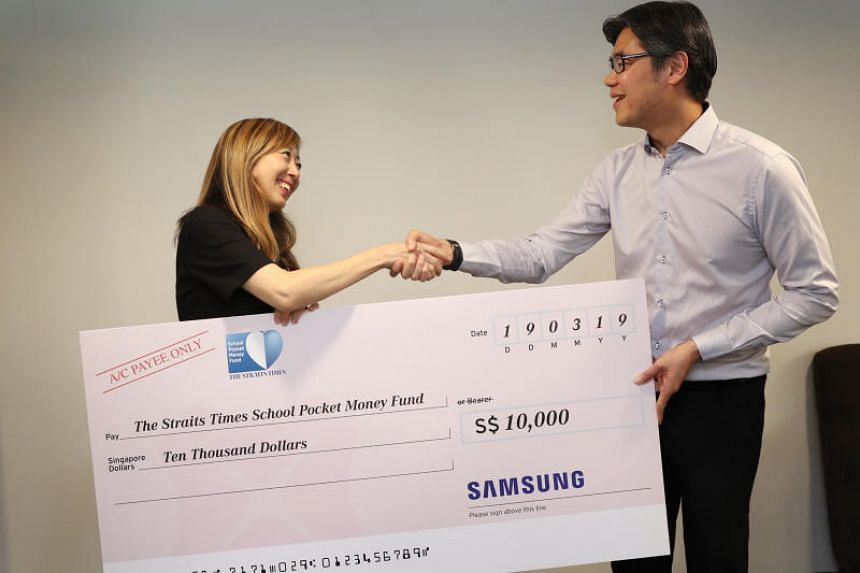 Ms Sumiko Tan, executive editor of The Straits Times, receiving a cheque from Mr Eugene Goh, president of Samsung Electronics Singapore, during the 4th HeadSTart outing on March 19, 2019.
