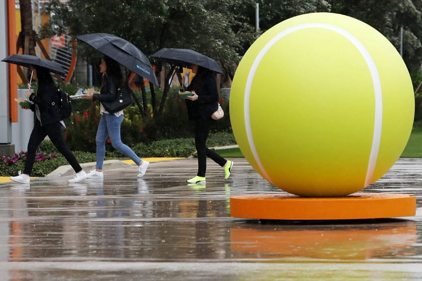People walk on the grounds past a giant tennis ball during a rain delay at the Miami Open tournament.