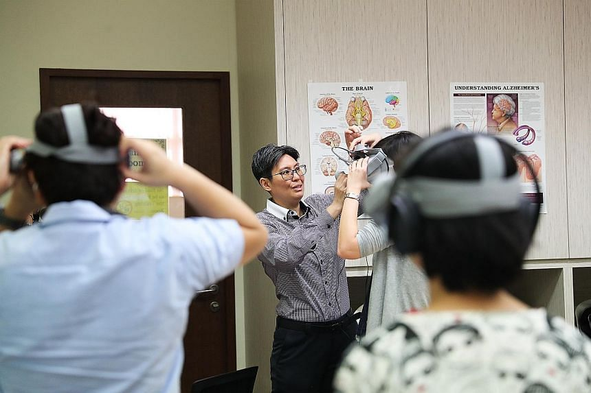 Ms Joanne Loy, a programme coordinator at the Alzheimer's Disease Association, helping a participant with a virtual reality headset at a workshop yesterday.