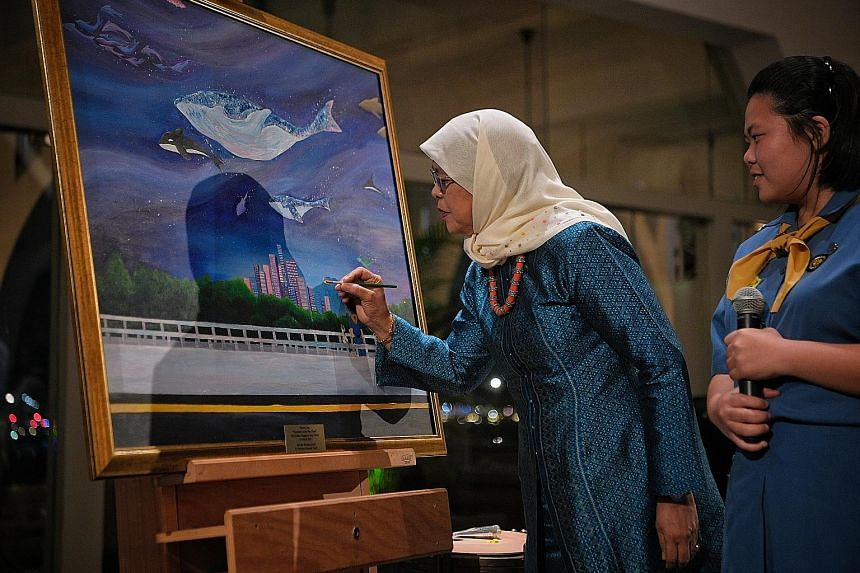 President Halimah Yacob adding a finishing touch to a painting done by Pasir Ris Crest Secondary School student Tammy Lim (right). The painting was one of 12 artworks for sale at yesterday's GGS Gala Dinner.