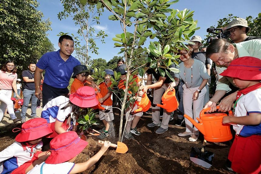 Second Minister for National Development Desmond Lee (in blue) joining around 50 pre-schoolers at a tree planting ceremony during the opening of the Nature Playgarden at HortPark yesterday. The new park, which has nine different play features, is par