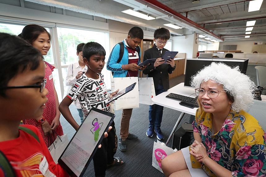 Zaheerul Hissham (far left) and Hahvenaas Poveneshwaran (third from left) with team members questioning Straits Times correspondent Rachel Au-Yong, who was playing the role of an old woman, during their visit to the newsroom yesterday. The beneficiar