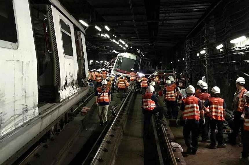 Emergency staff at work yesterday at the site where two of Hong Kong's MTR trains collided during a test run inside a tunnel on Monday. MTR operations director Adi Lau Tin-shing said the nature of the accident and the damage done to the trains made r