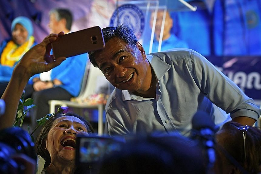 Thailand's former prime minister Abhisit Vejjajiva posing for a selfie with a supporter at a Democrat Party rally on Monday at Bangkok's Crystal Design Centre.