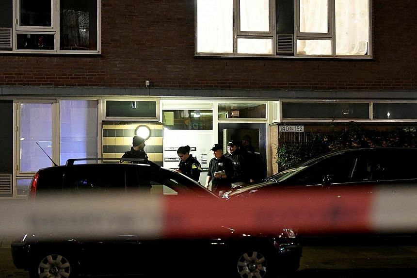 Police officers at the building in Utrecht on Monday where Gokmen Tanis, the main suspect in the shooting in the Dutch city on the same day, was arrested after a seven-hour manhunt. Flowers placed yesterday at the site of Monday's shooting in Utrecht