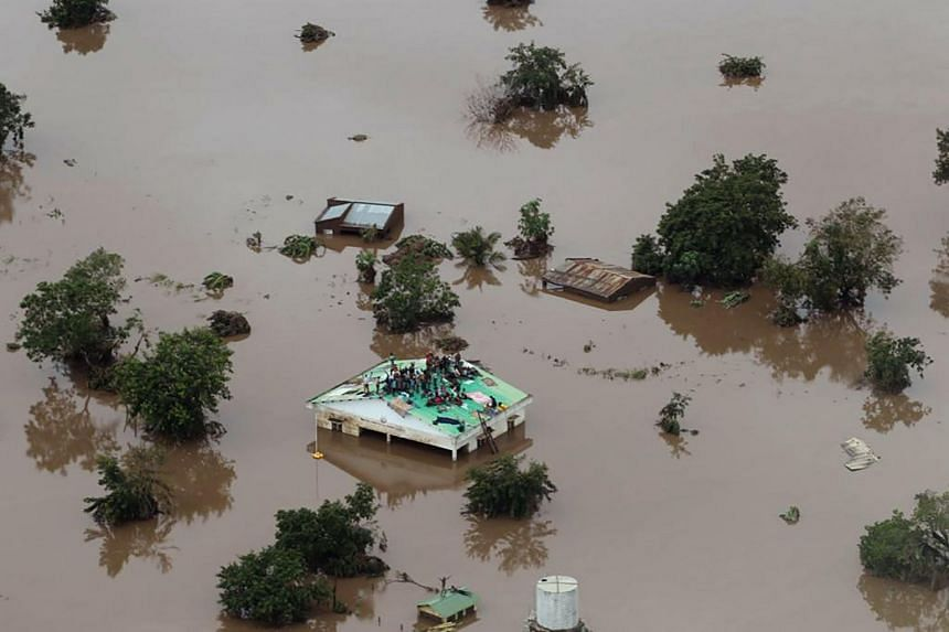 People on a roof surrounded by flooding in an area affected by Cyclone Idai in Beira, on March 18.