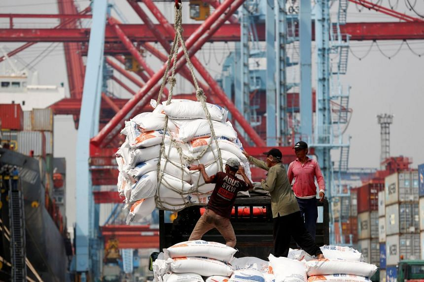 Workers unload bags of rice from a cargo ship onto a truck at Tanjung Priok Port in Jakarta, Indonesia, on April 16, 2018.