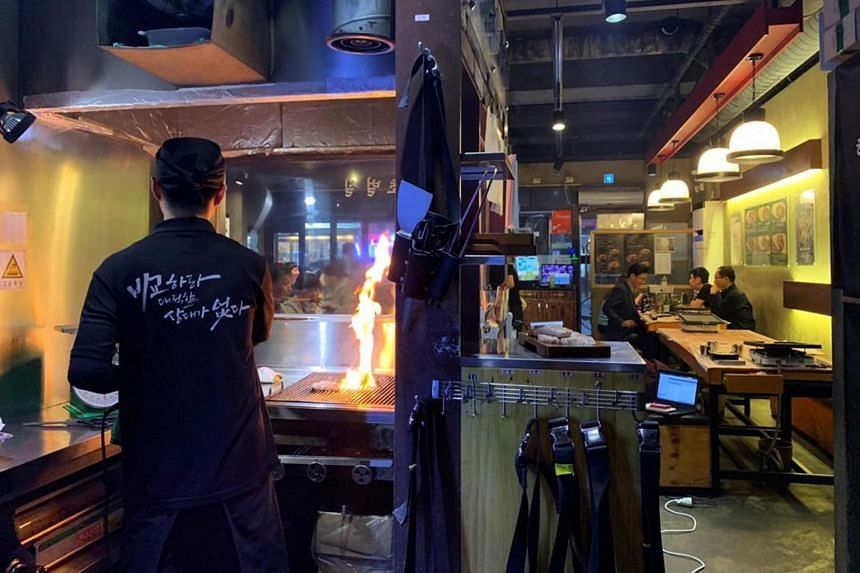 An employee roasts pork at a Korean BBQ restaurant in Seoul, South Korea, on March 13, 2019.