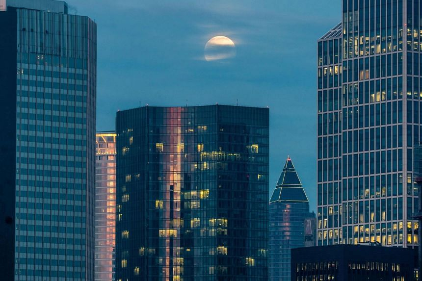 A full moon setting behind skyscrapers of the banking district in Frankfurt am Main, western Germany, on Feb 20, 2019.