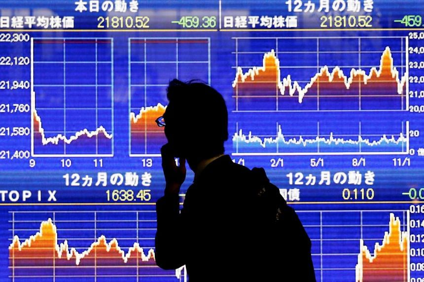 A man looks at an electronic stock quotation board showing Japan's Nikkei average outside a brokerage in Tokyo, Japan, on Nov 13, 2018.
