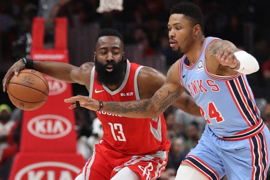 Houston Rockets guard James Harden drives against Atlanta Hawks guard Kent Bazemore at State Farm Arena in Atlanta on March 19, 2019.