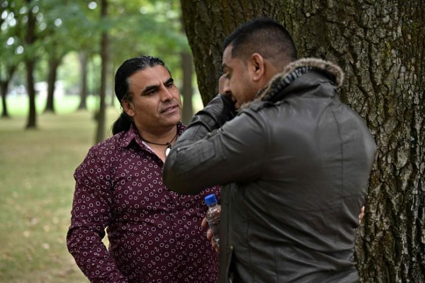Afghan refugee and local resident Abdul Aziz (left) speaking with a man who came to thank him for his bravery during an interview with AFP in Christchurch on March 17, 2019, two days after he chased a gunman at Linwood Mosque.