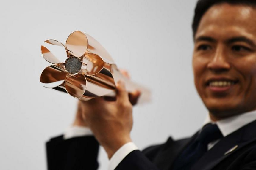 Torch Relay Ambassador Tadahiro Nomura presents the Tokyo 2020 Olympic Games torch for the torch relay in Tokyo on March 20, 2019.