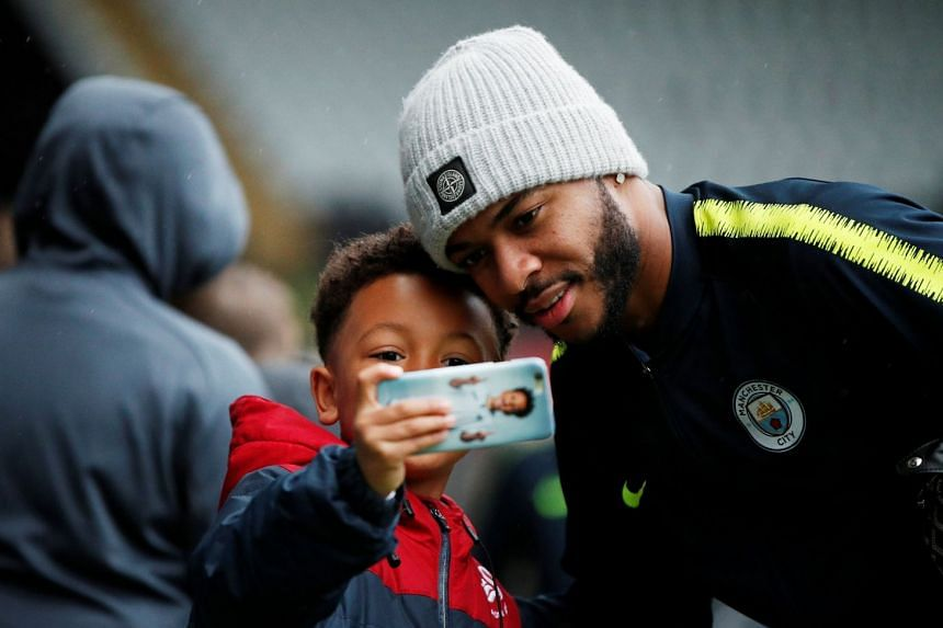 Manchester City's Raheem Sterling poses for a selfie with fans before a match.