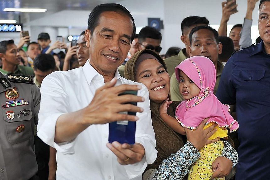 President Joko Widodo meeting supporters during a visit to an upcoming train station.
