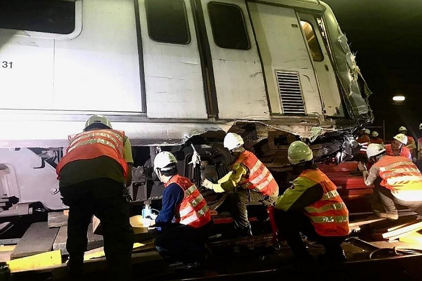Engineers inspecting a damaged MTR train after it collided with another one during a test run inside a tunnel on Monday. The accident led to a two-day service disruption on the Tsuen Wan Line between Central and Admiralty stations.