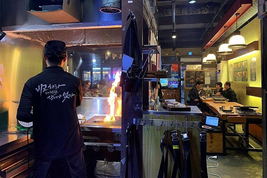 An employee of a Korean barbecue restaurant in Seoul roasting pork. The sale of pork rises when air pollution worsens in South Korea. The correlation stems from an old belief attributed to coal miners that the slippery pork oil helps cleanse dirt fro