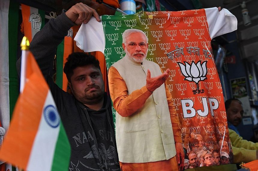 As election fever builds up, a shopkeeper in New Delhi shows a T-shirt with a picture of Prime Minister Narendra Modi printed on it.