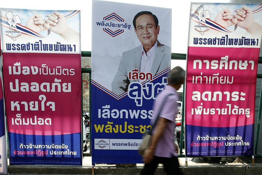 A pedestrian walks past an election campaign poster of pro-junta political party Palang Pracharath featuring a portrait of Thai Prime Minister and junta leader Prayut Chan-o-cha, in Bangkok, Thailand, 21 March 2019.
