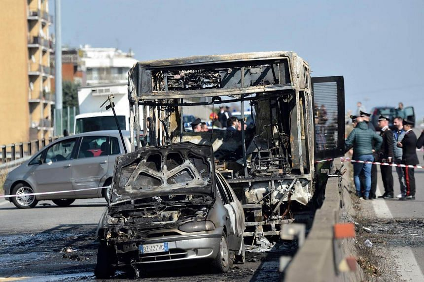The wreckage of a school bus that was transporting some 50 children after it was torched by the bus' driver, in San Donato Milanese, Italy.