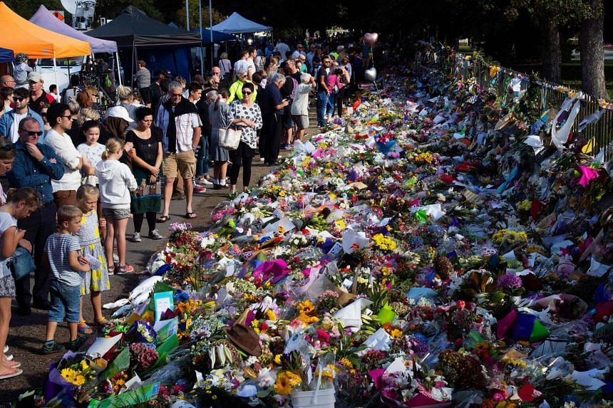 Visitors look at floral tributes for the victims of the Christchurch attacks at the Botanical Garden in Christchurch, on March 19, 2019.