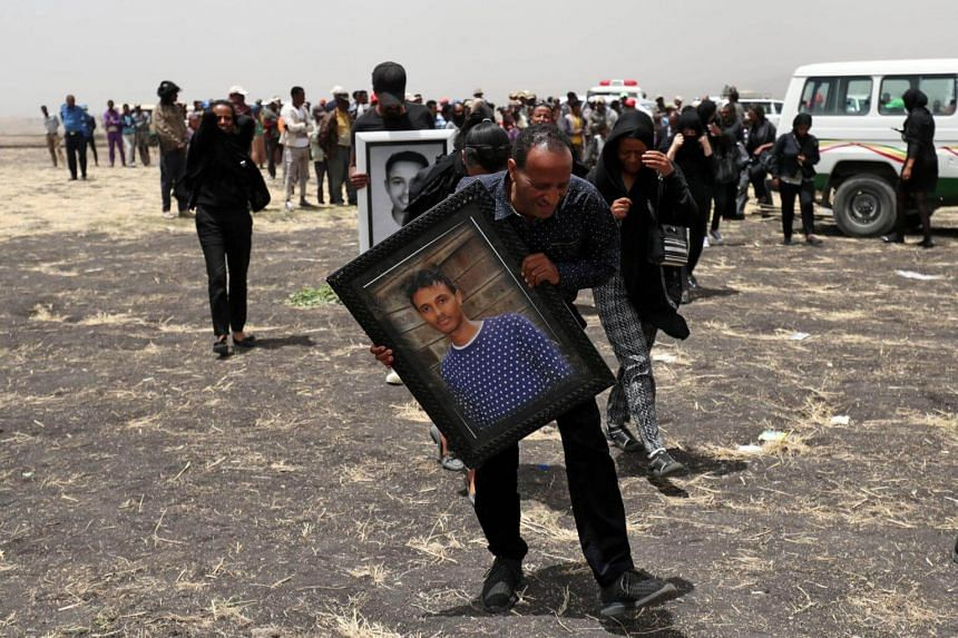 A relative carries a portrait photograph of Ethiopian Airlines pilot Yared Getachew as he mourns at the scene of the plane crash, on March 14, 2019.