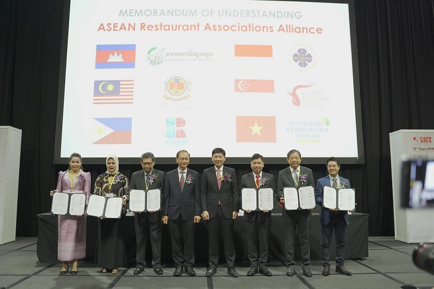 Senior Minister of State for Trade and Industry Chee Hong Tat (fourth from right) and Enterprise Singapore deputy chief executive Ted Tan (fifth from right), with representatives from the respective Asean restaurant associations after the MOU signing