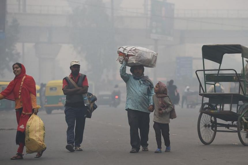 A family carries belongings while looking for a rickshaw amid heavy smog in New Delhi on Nov 5, 2018. New Delhi is the world's most polluted major city.