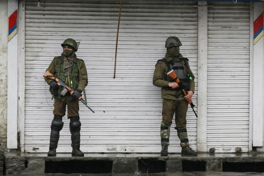 Indian paramilitary Central Reserve Police Force personnel standing guard outside a building in Indian Kashmir, on March 20, 2019.