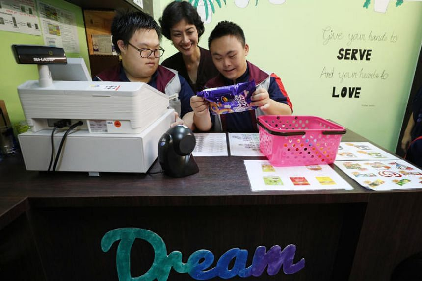 Minds students Milford Loh (left) and Tan Jun Jie (right) serving customers in a minimart on March 21, which is World Down Syndrome Day, as MP for Tanjong Pagar GRC, Ms Joan Pereira, looked on. The minimart at the Minds Lee Kong Chian Gardens School