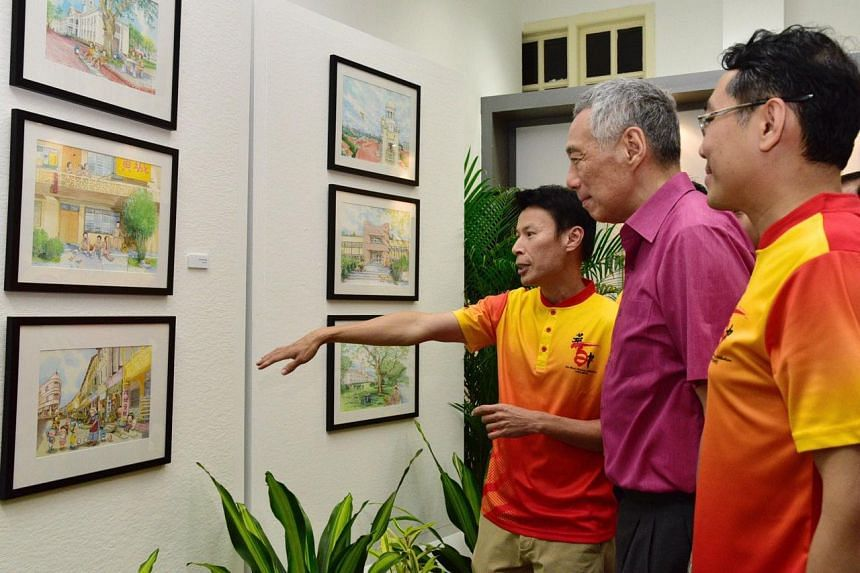 (From left) Artist Lee Kow Fong showing his watercolour illustrations to Prime Minister Lee Hsien Loong and Hwa Chong Institution principal Pang Choon How.
