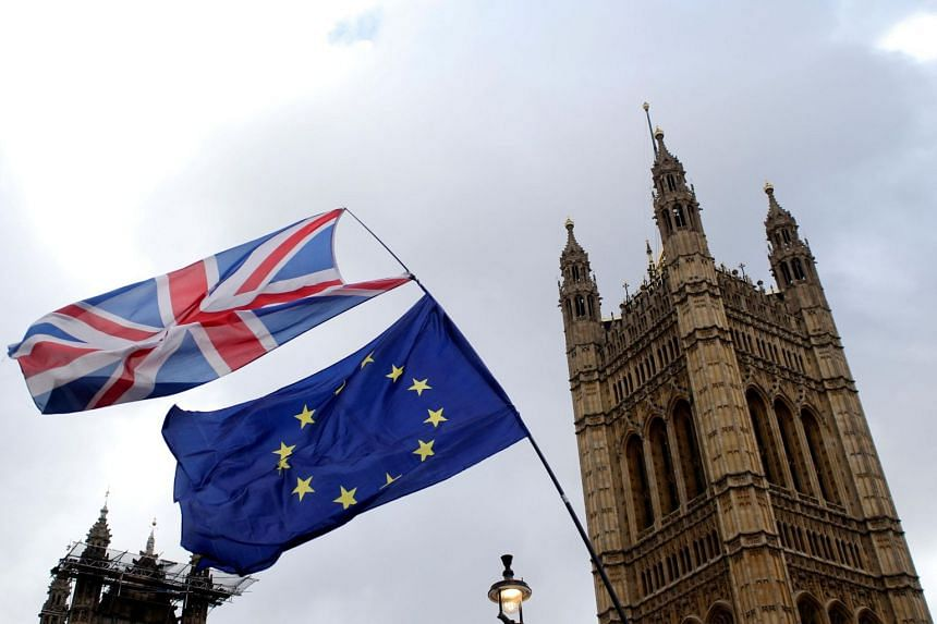 Flags flutter outside the Houses of Parliament, ahead of a Brexit vote, in London, Britain, on March 13, 2019.