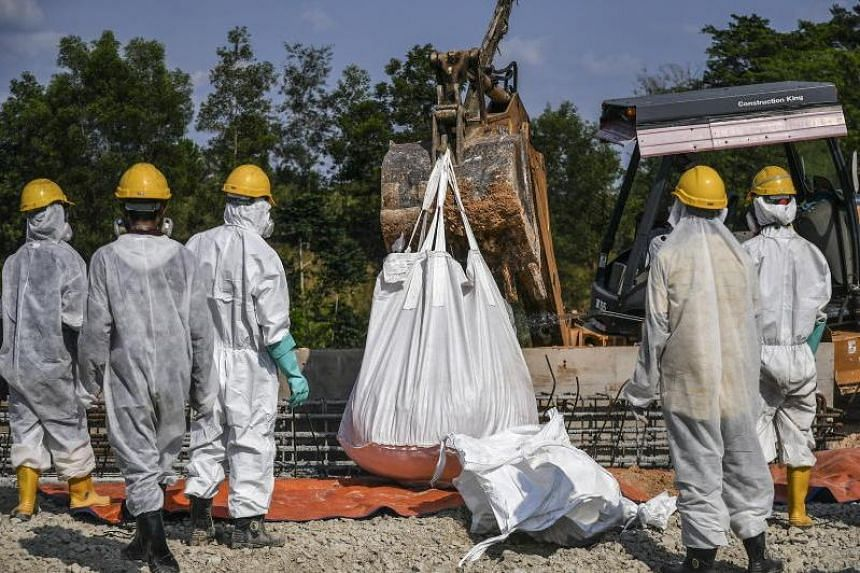 Emergency personnel in protective suits prepare to clean up the Sungai Kim Kim river in Pasir Gudang, Malaysia, on March 14, 2019.