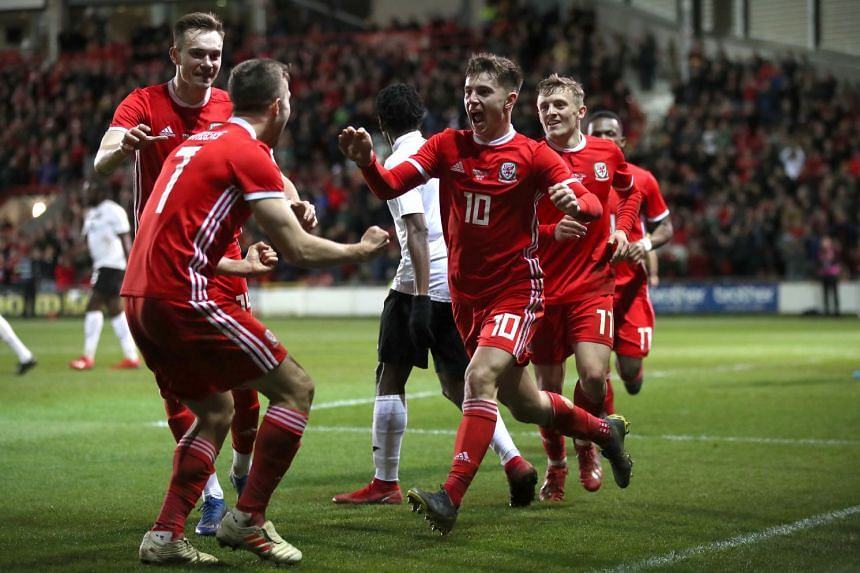 Wales' Ben Woodburn (C) celebrates with his teammates after scoring his side's first goal.
