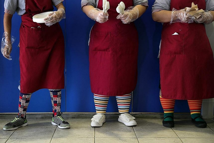 Minds adult beneficiaries wearing colourful socks to mark World Down Syndrome Day yesterday. Milford Loh (far left), 17, and Tan Jun Jie, 16, serving as cashiers at the minimart in Minds Lee Kong Chian Gardens School during its World Down Syndrome Da