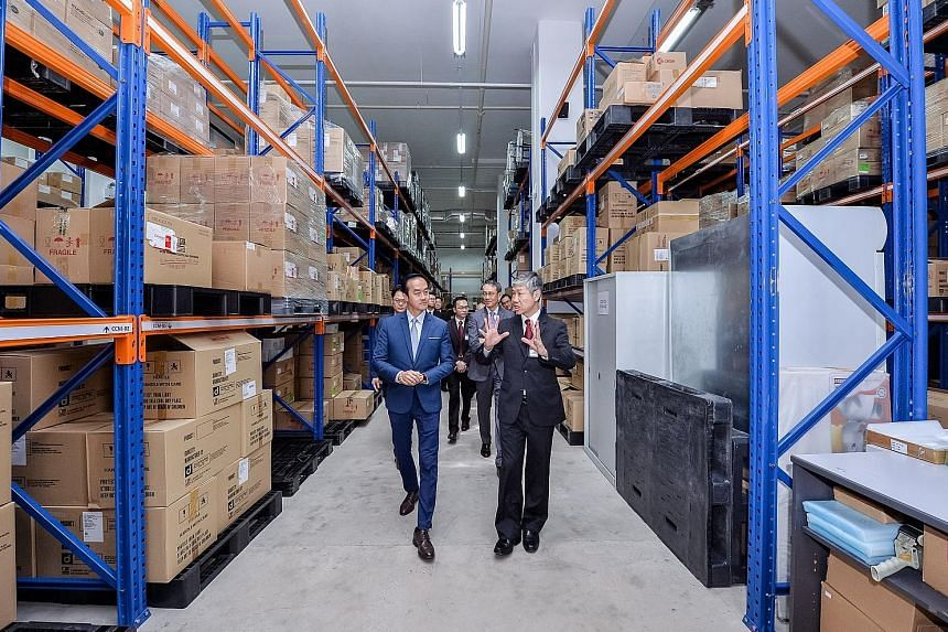 Senior Minister of State for Trade and Industry Koh Poh Koon (in blue), being briefed by Hyphens Pharma International chairman and CEO Lim See Wah yesterday, during a tour of the firm's new facility, which houses an automated packaging line with equi